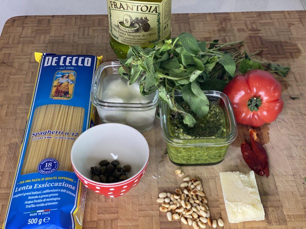 Packung Spaghetti, Kapern, Pesto, Tomate, Parmesan und Basilikum