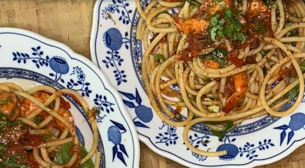 Zwei Teller mit Bucatini und Tomatensauce mit Garnelen