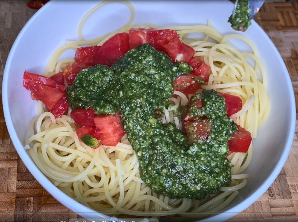 Schüsseln mit gekochten Spaghetti, Tomaten und Pesto