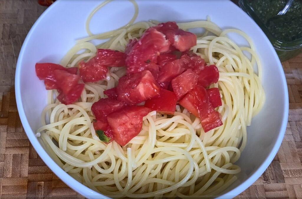 Schüssel mit gekochten Spaghetti und gehackten Tomaten