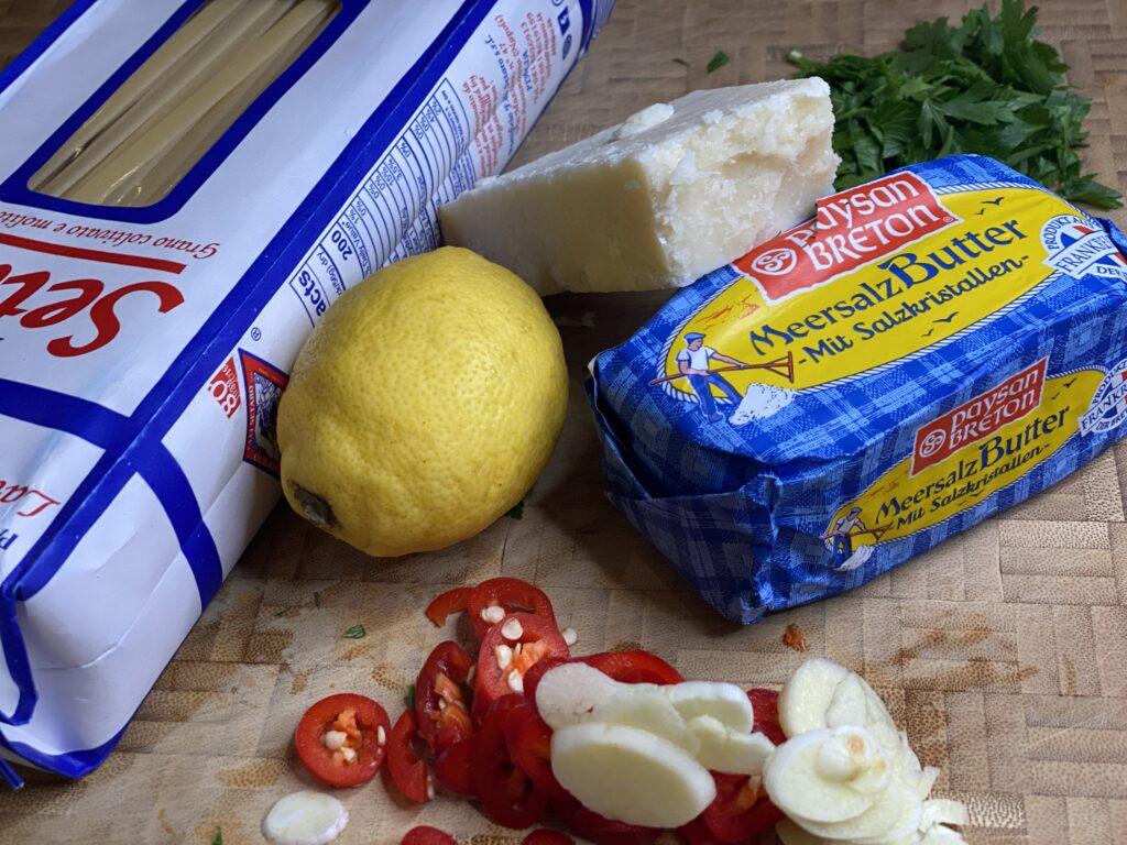 Butter, Zitrone, Spaghettipackung, Parmesan und kleingeschnittete Chili und Knoblauchzehen