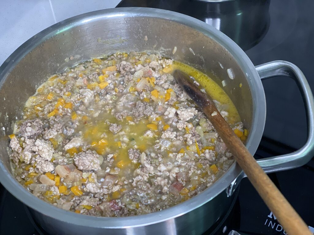 Topf mit Hackfleisch und Gemüse in Brühe