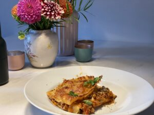 Teller Lasagne Bolognese auf Tisch mit Blumenvase