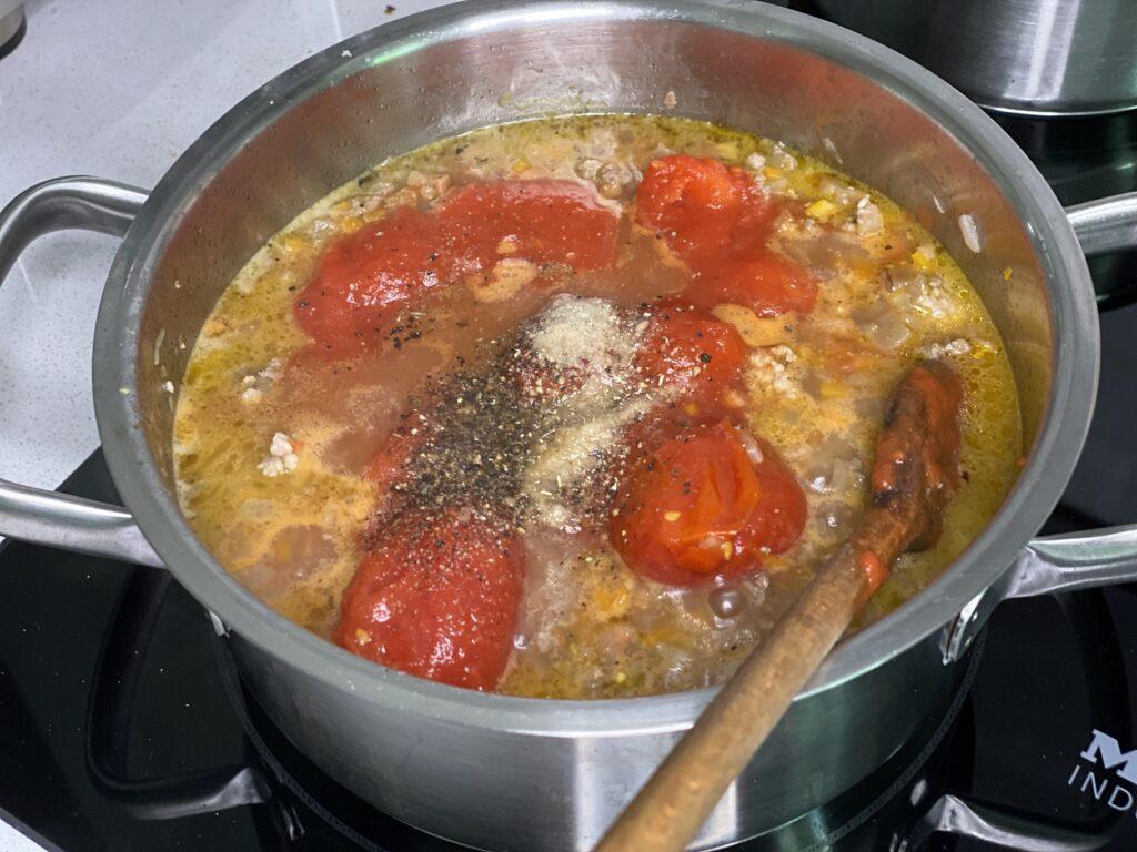 Topf mit Fleischsoße und Tomaten